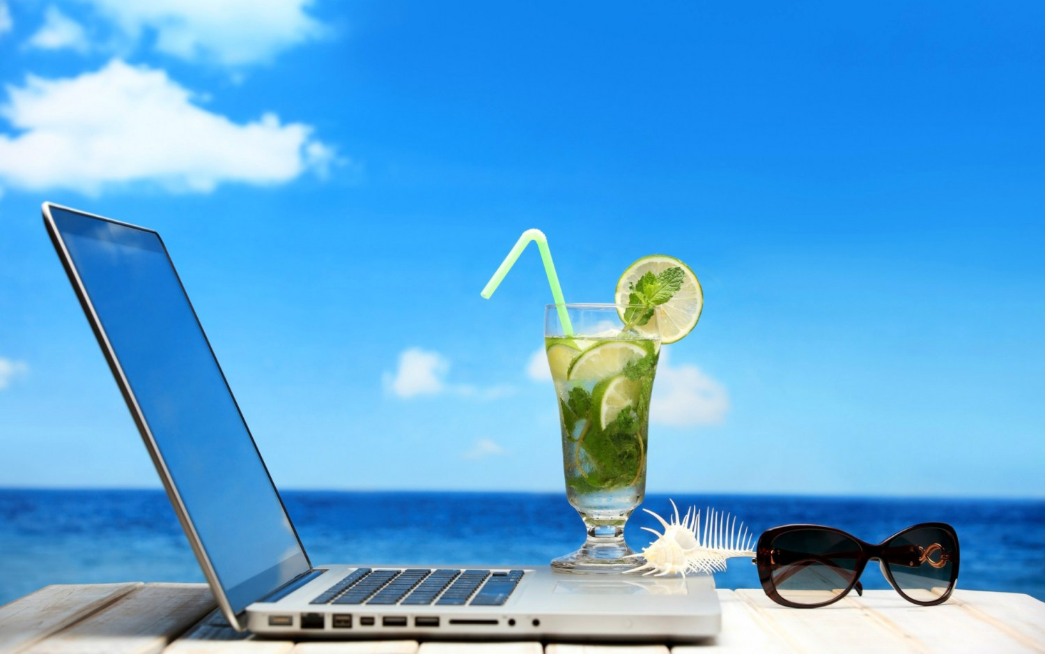 table with laptop, drink, and sunglasses with ocean and blue sky in background