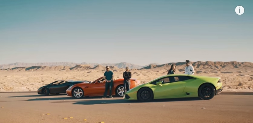 group of people standing in front of 3 supercars